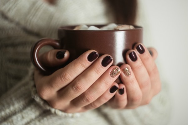 Brown cup with cocoa and marshmallow in the hands of the girl. Manicure gel nail.